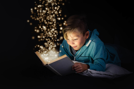 blond boy reading a magicical story book with light leaping off the page